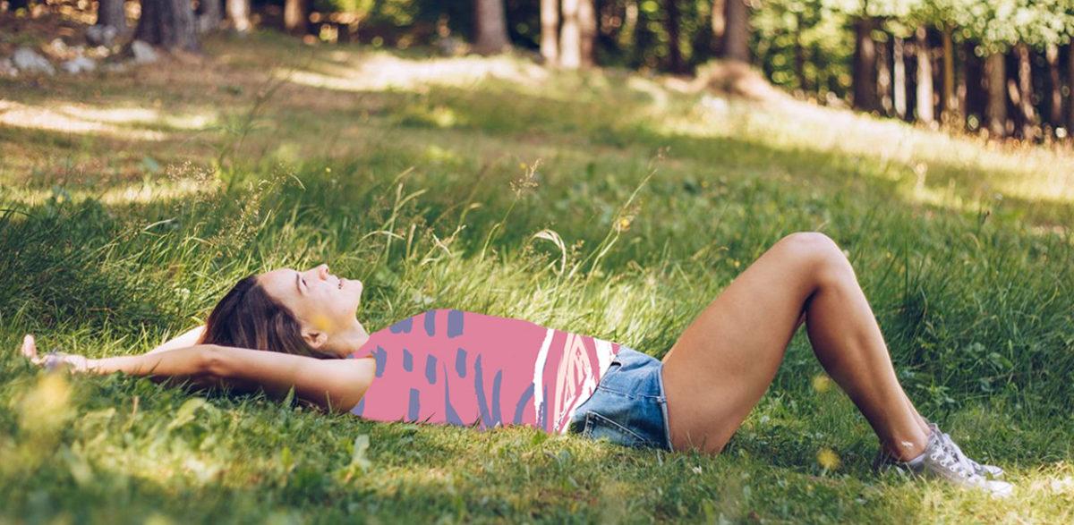 Jeune femme allongée en forêt qui se repose et admire le ciel