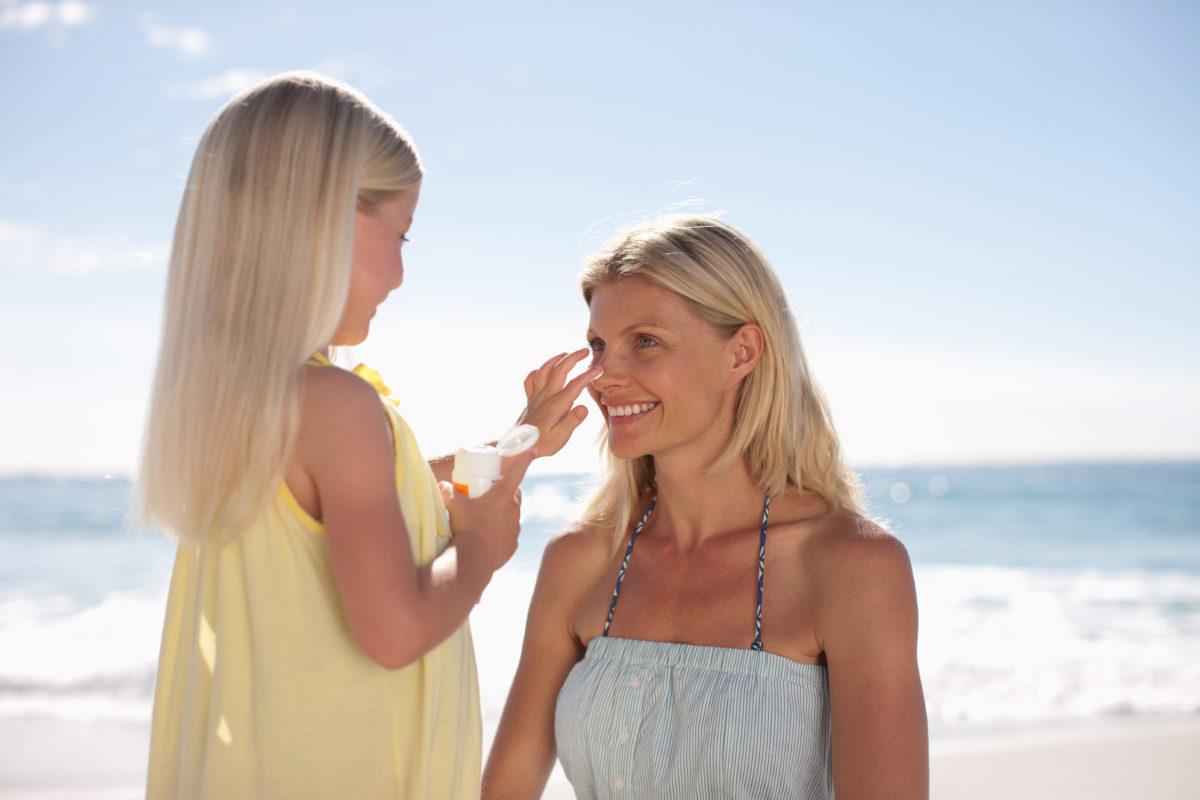 Fille et mère sur la plage au bord de la mer qui se protègent du soleil avec crème protectrice
