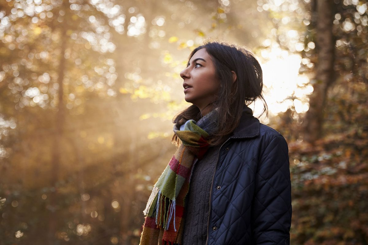Femme dans les bois respirant l'air frais avec le soleil durant l'hiver