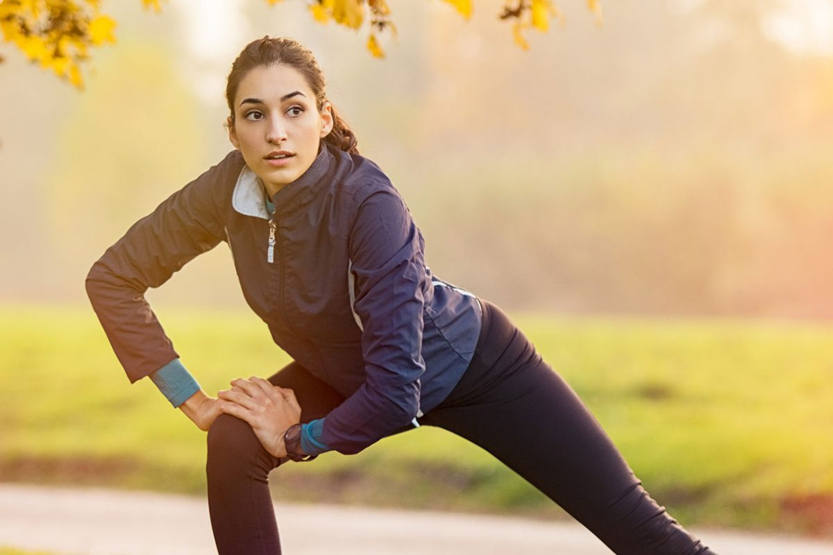 Jeune femme après séance de course à pied qui s'étire en pleine nature - 1320x880