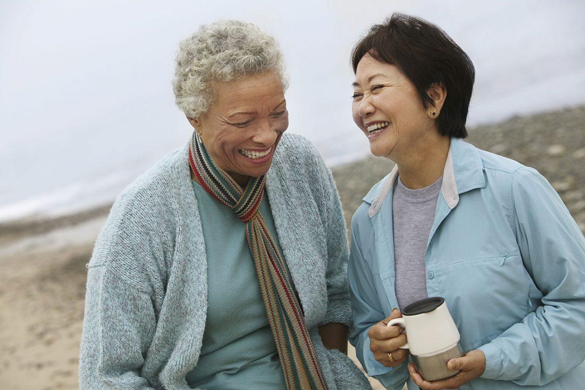 Femmes durant période ménopause souriantes au bord de la mer