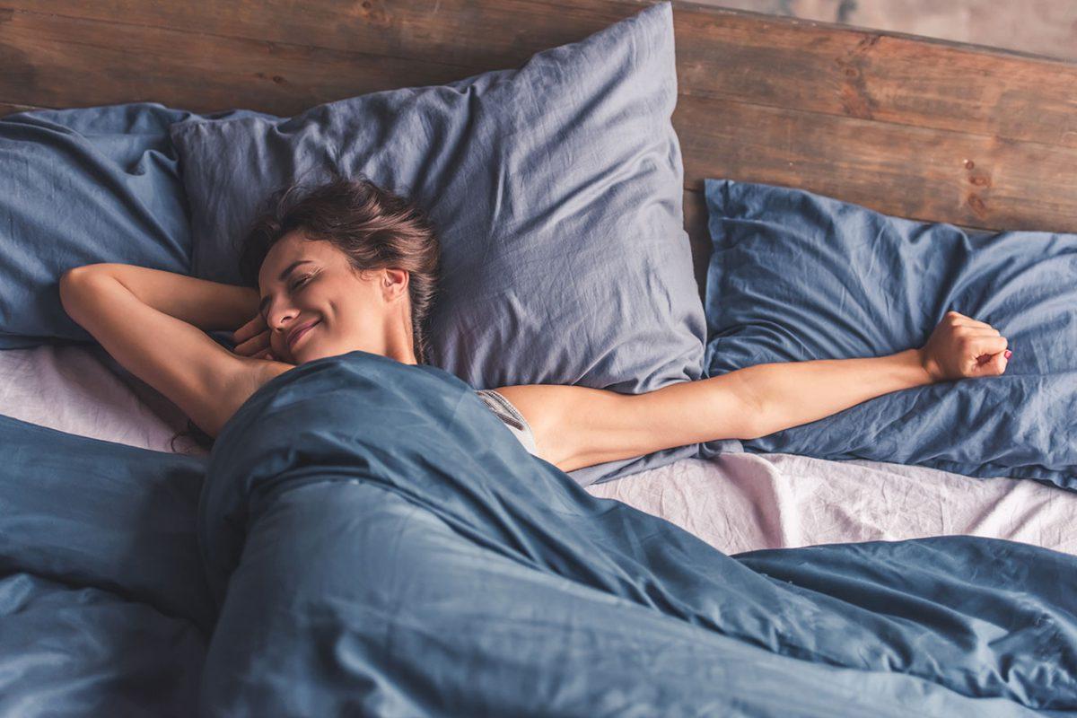 Jeune femme qui se réveille dans son lit en s'étirant