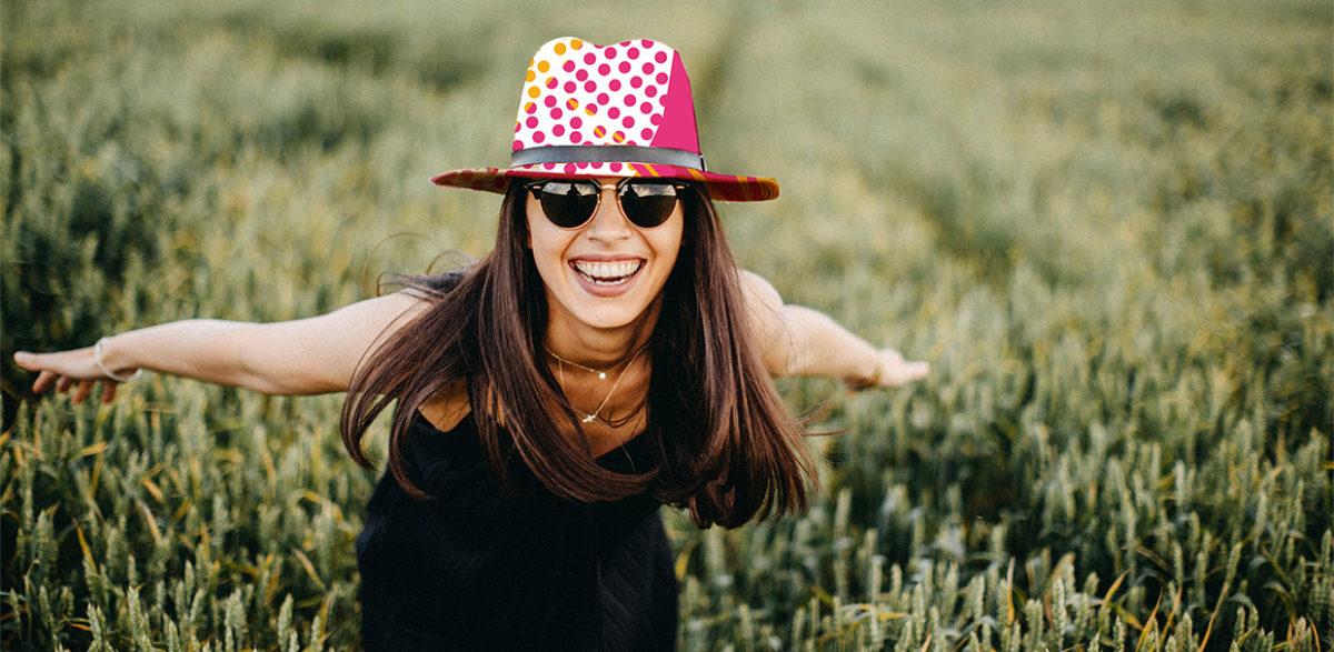 Femme avec chapeau et lunettes de soleil les bras tendus et ouverts dans un champ