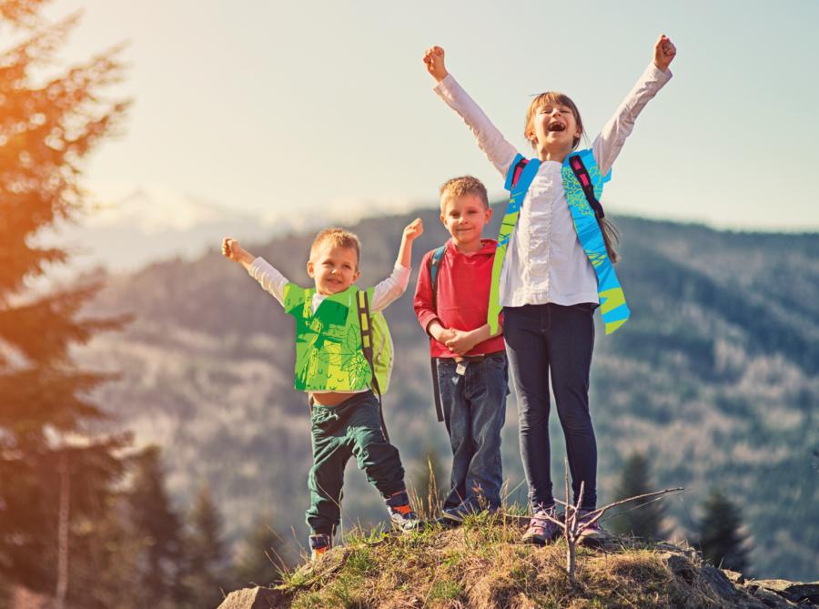 Trois jeunes enfants heureux dans les montagnes levant les bras au ciel, profitant du soleil et de la nature - 900x669