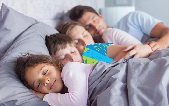 Famille complète dormant dans le lit parental