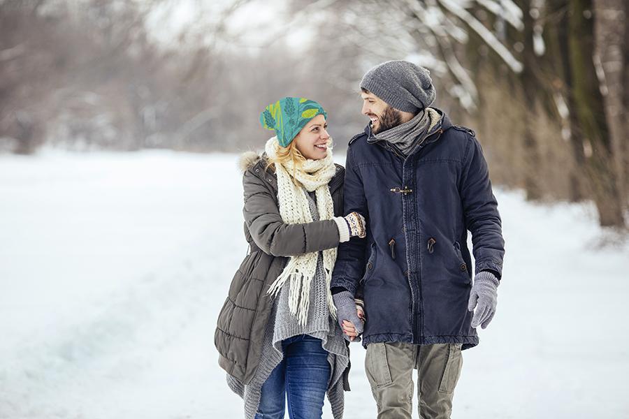 Jeune couple heureux qui se promène dans la neige dans un parc boisé