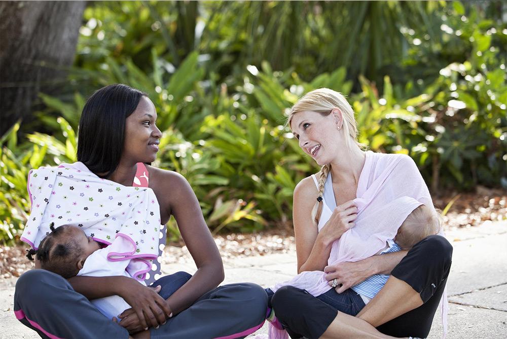 2 jeunes mamans assises proche verdure en train d'allaiter