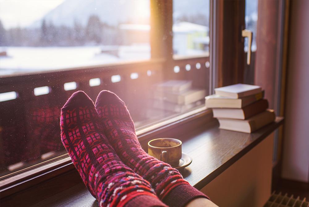 plan rapproché sur les pieds d'une femme avec chaussettes face à la montagne avec neige