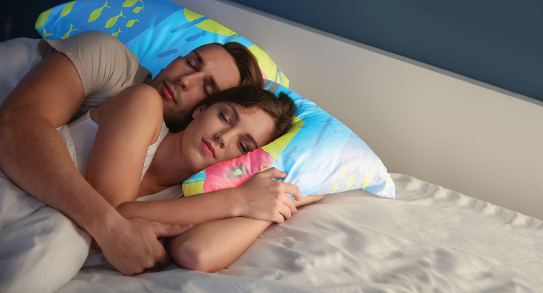 Couple dormant enlacé paisiblement dans le lit