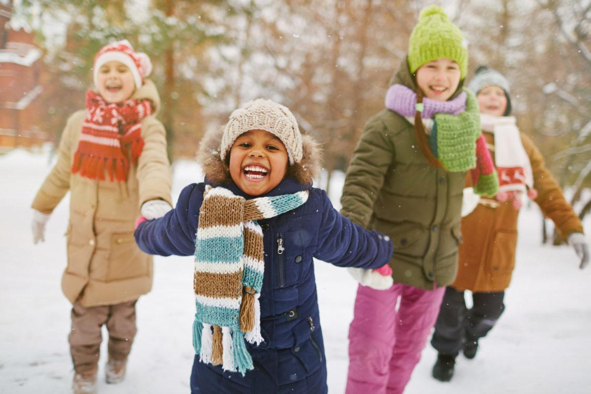 4 jeunes enfants main dans la main s'amusant dans la neige