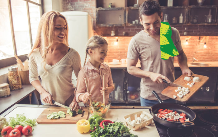 Couple avec leur fille dans la cuisine en train de préparer un plat à base de légumes