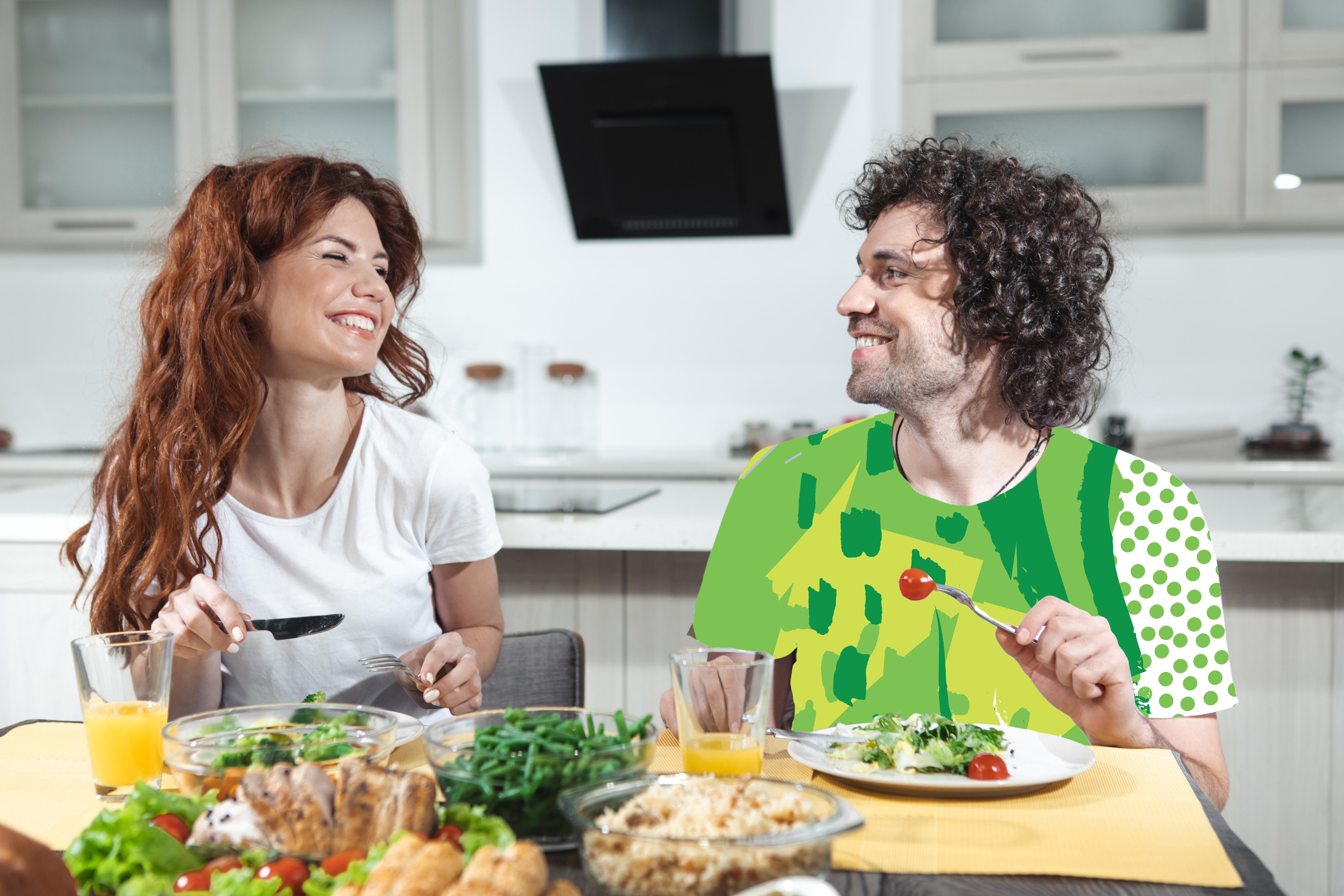 Couple dans cuisine en train de déguster une salade avec des produits frais et un jus de fruits
