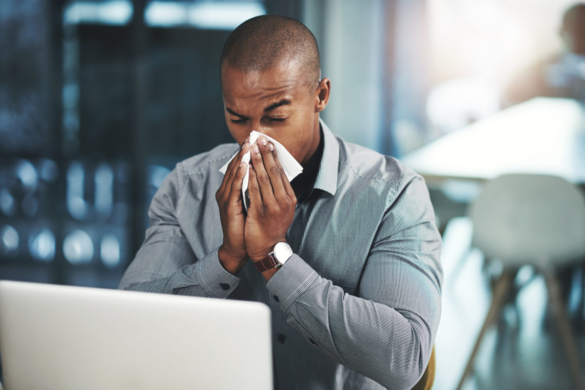 Jeune homme d'affaires au bureau devant son ordinateur en train de se moucher