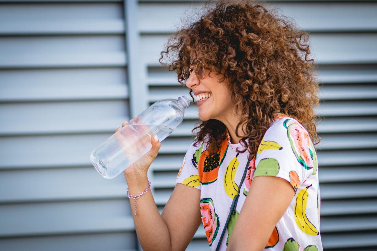 Jeune femme souriante buvant une grande bouteille d'eau en extérieur