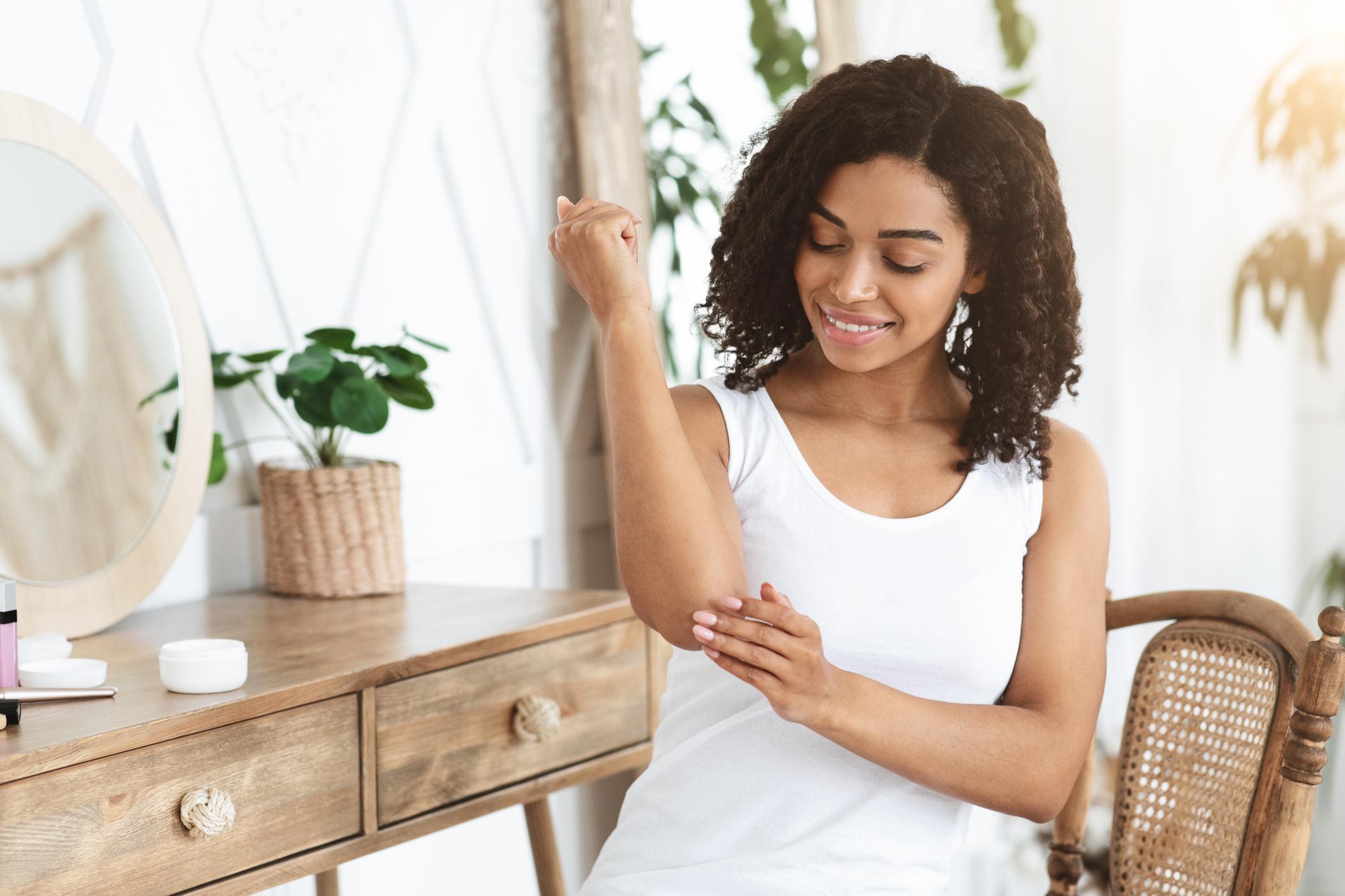 Jeune femme appliquant une crème hydratante pour réparer les coudes secs et protéger la peau fissurée