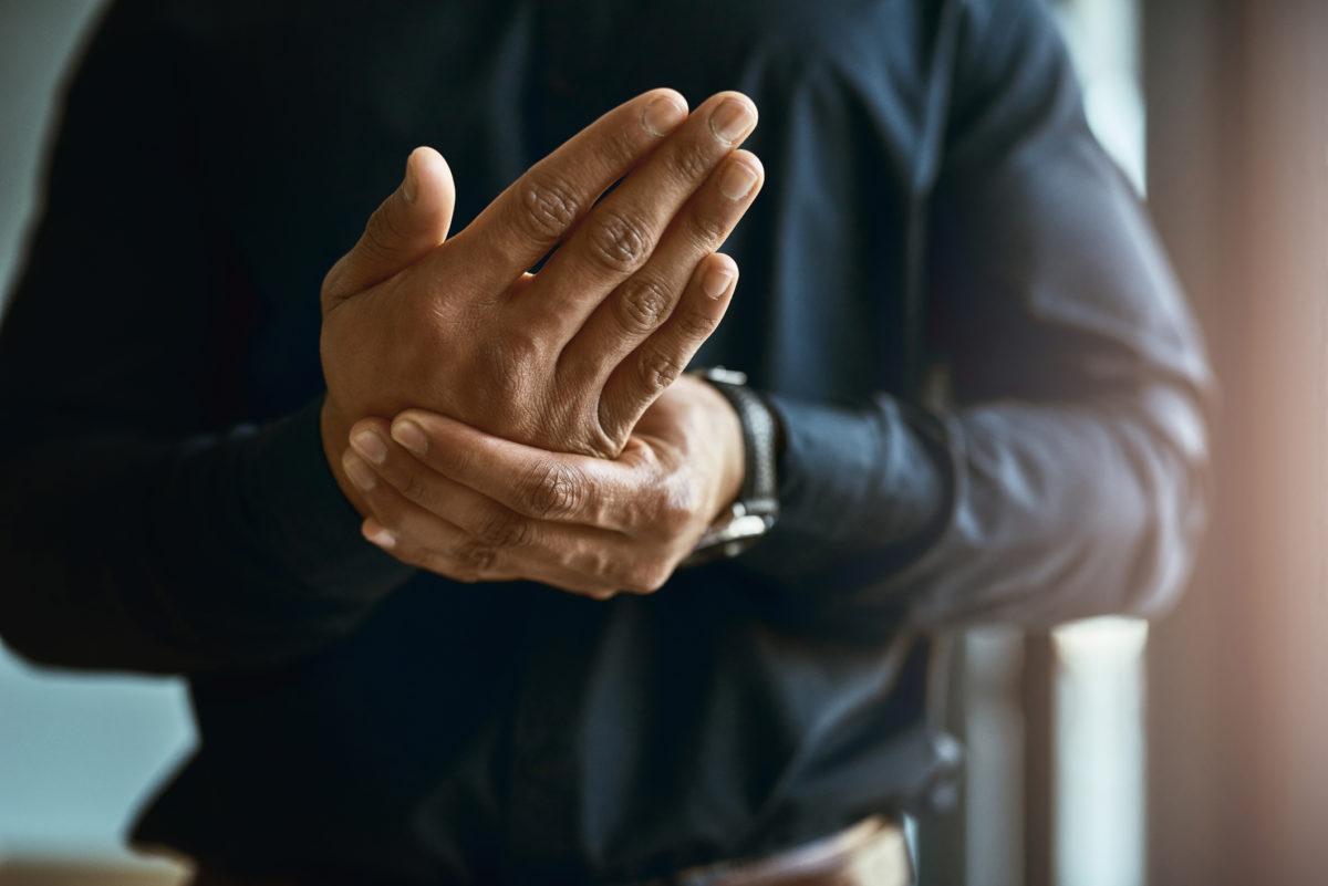 Plan rapproché sur les main d'un homme d'affaires souffrant d'engourdissement et de douleurs dans les mains