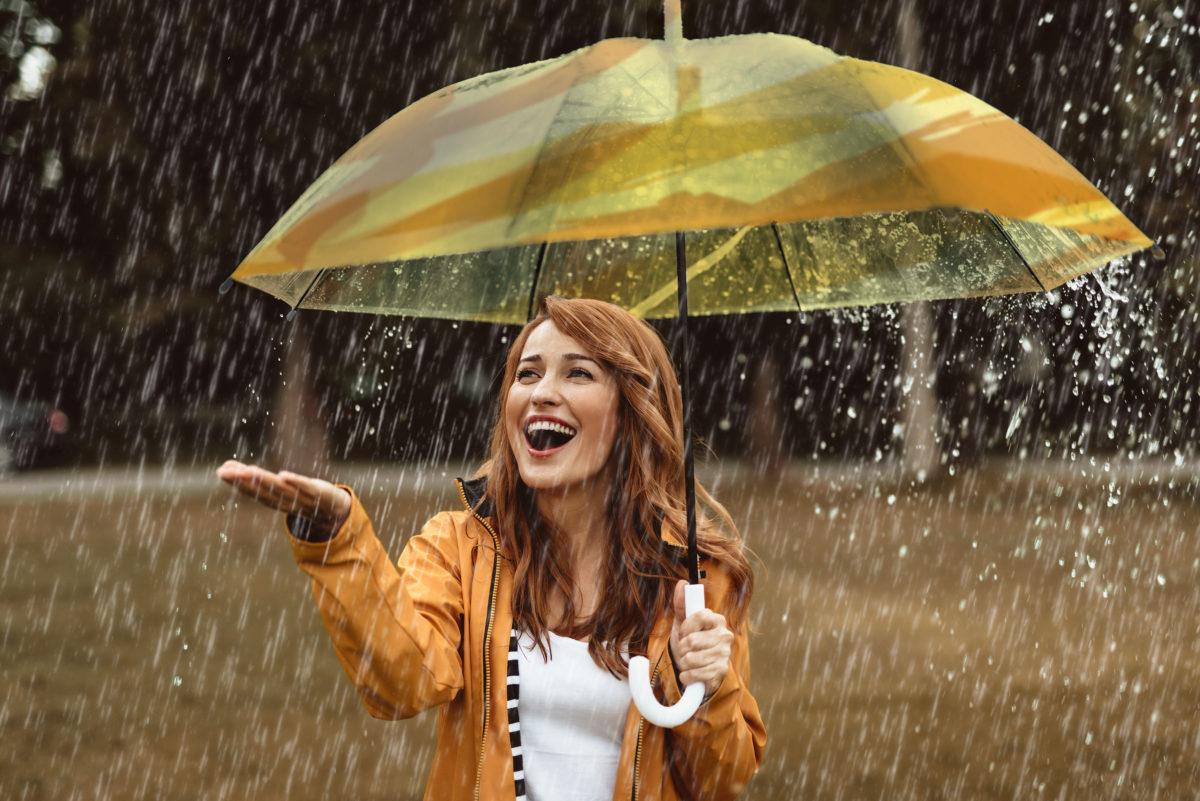 Jeune femme souriante sous parapluie jaune mettant la main sous la pluie