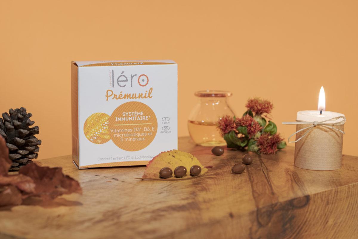 Boite capsules Prémunil Léro sur meuble en bois avec bougies, feuilles et pommes de pin