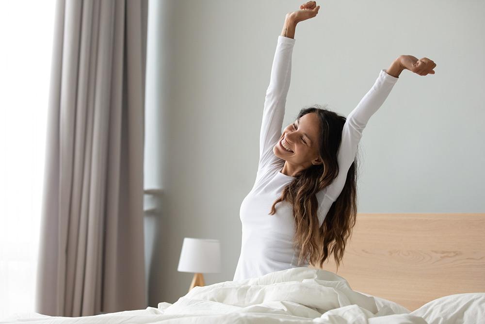 Jeune femme souriante qui se réveille de bonne humeur et en forme