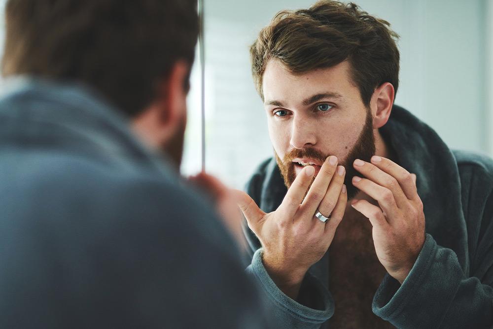Jeune homme devant miroir observant les défauts sur sa peau