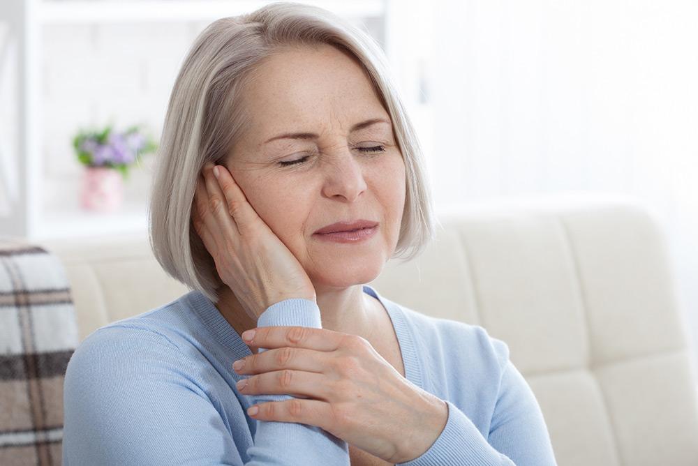 Femme fermant les yeux et souffrant d'acouphènes