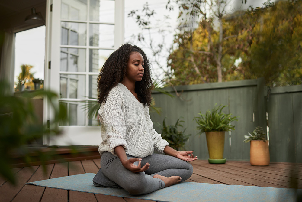 Jeune femme sur terrasse en bois pendant séance de yoga en position du lotus