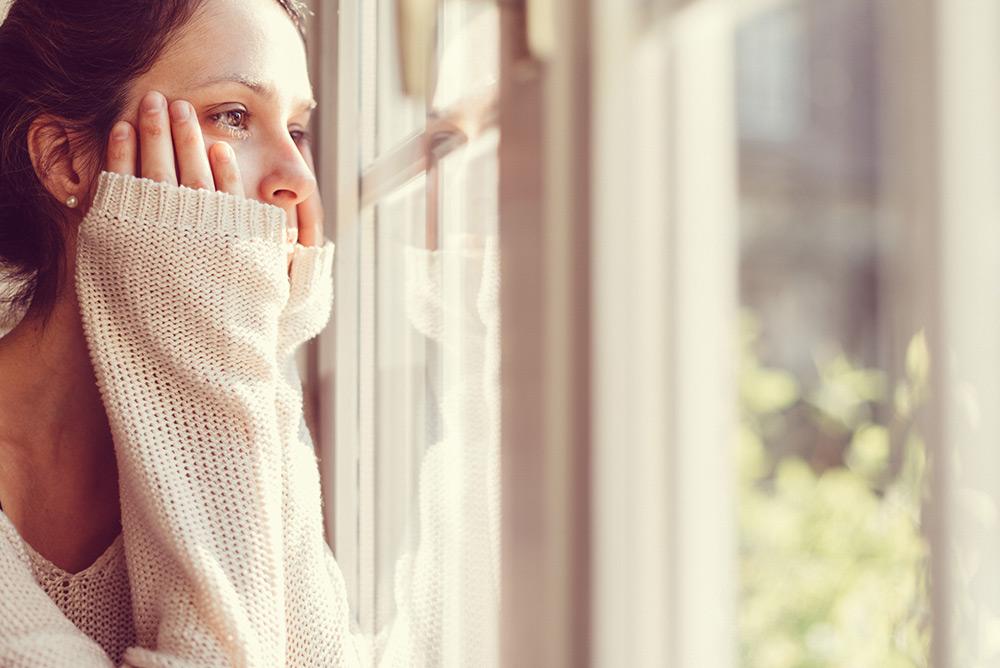 Jeune femme déprimée regardant par la fenêtre