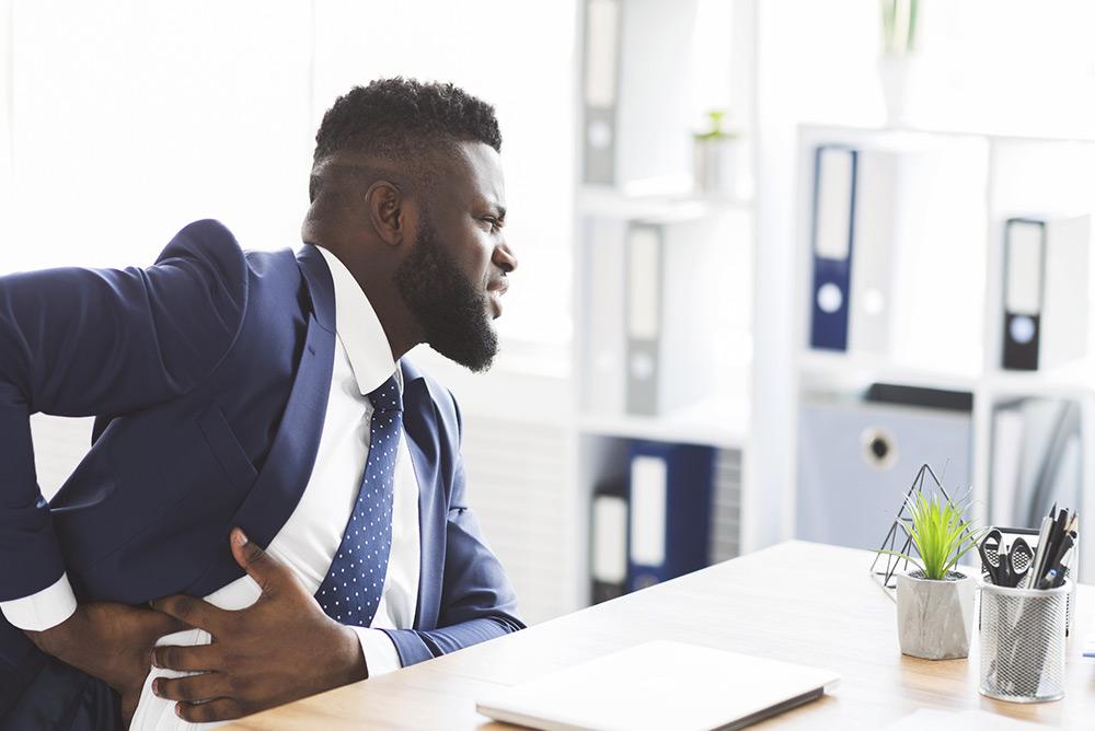 Jeune homme au bureau souffrant d'une crise de foie, avec des douleurs au niveau des côtes