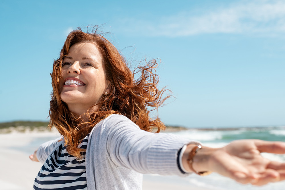 Femme souriante et heureuse les bras ouverts sur une plage au bord de la mer