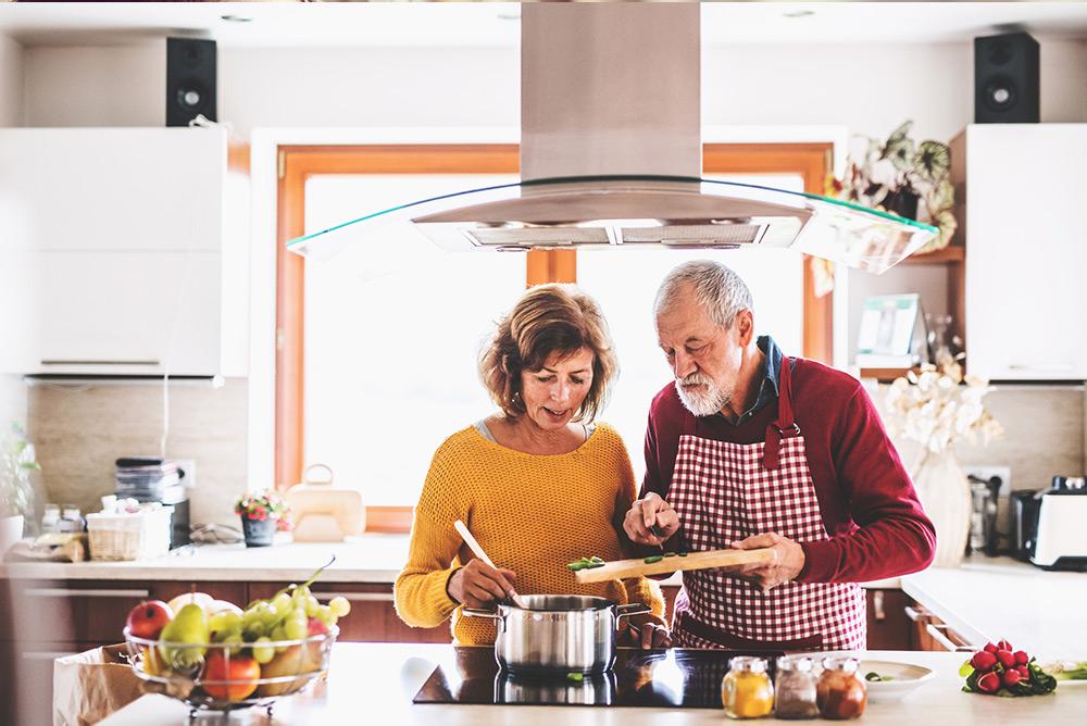 Couple en cuisine préparant des plats avec légumes