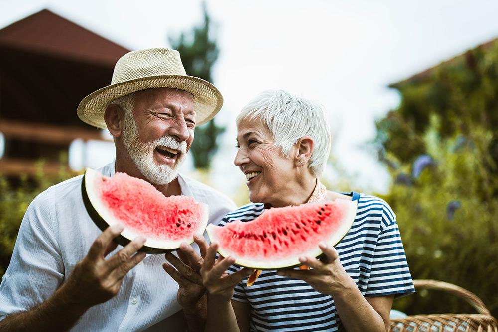 Couple à la retraite heureux dégustant une pastèque