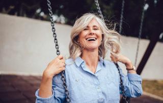 Femme souriante et bien dans son corps sur une balançoire