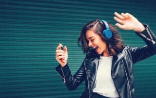 Jeune femme écoutant de la musique avec casque heureuse et énergique
