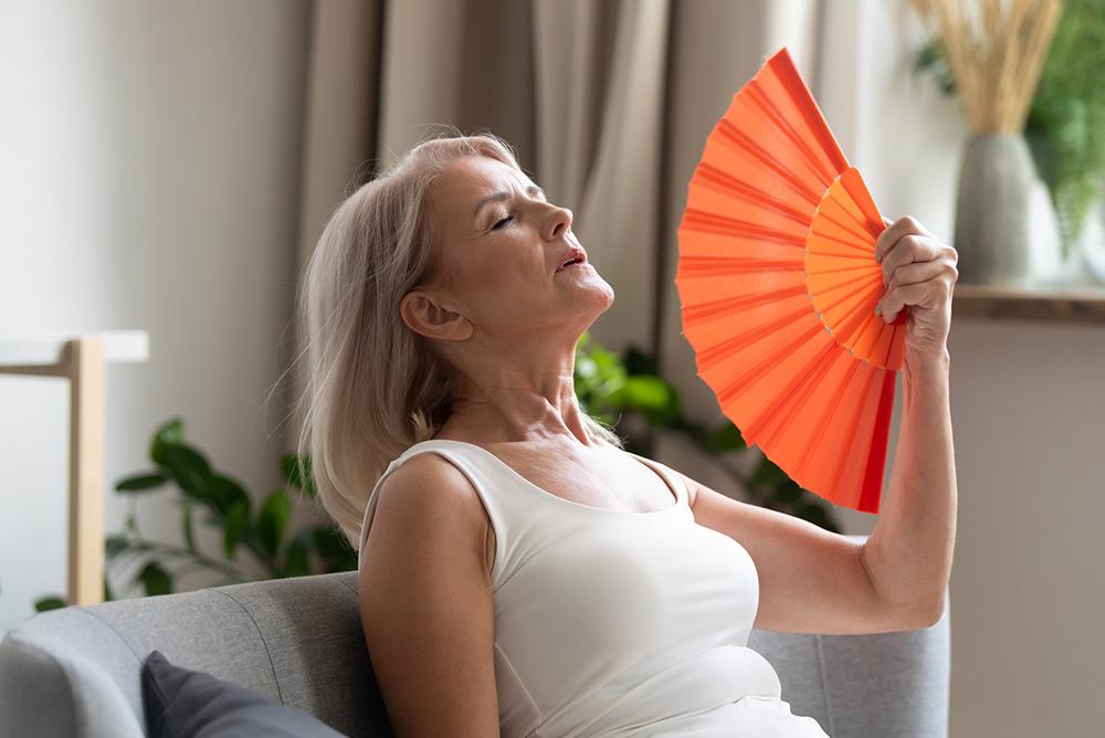 Femme assise sur un canapé ayant des bouffées de chaleur avec un éventail dans la main