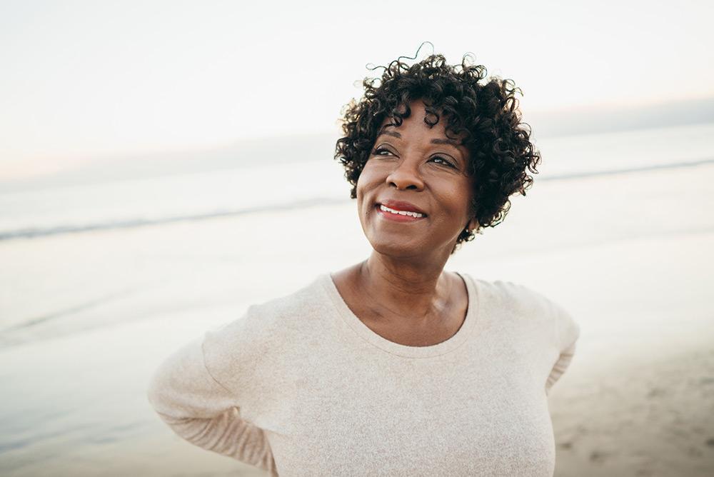 Femme souriante sur la plage au bord de l'eau prenant le temps d'admirer le paysage et de profiter du cadre