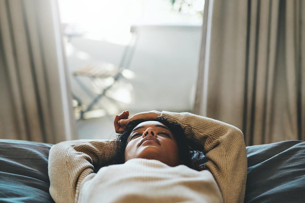 Jeune femme fatiguée qui ferme les yeux allongée sur le canapé
