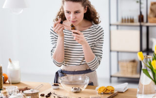 Jeune femme en cuisine préparant un plat sentant un flacon d'huiles essentielles