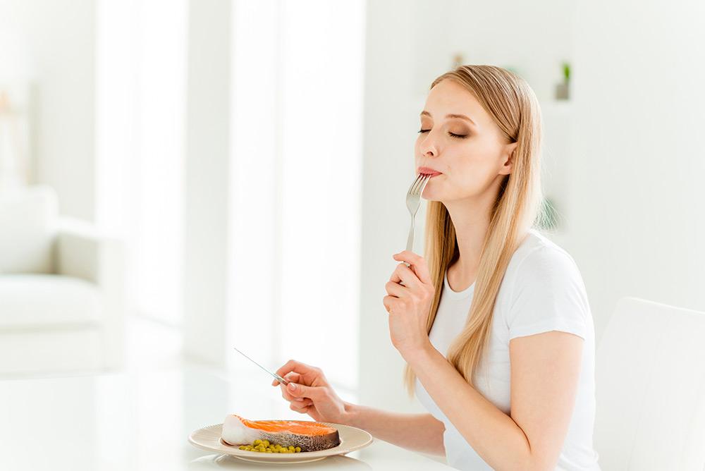 Jeune femme qui savoure un plat sain et équilibré dans la cuisine