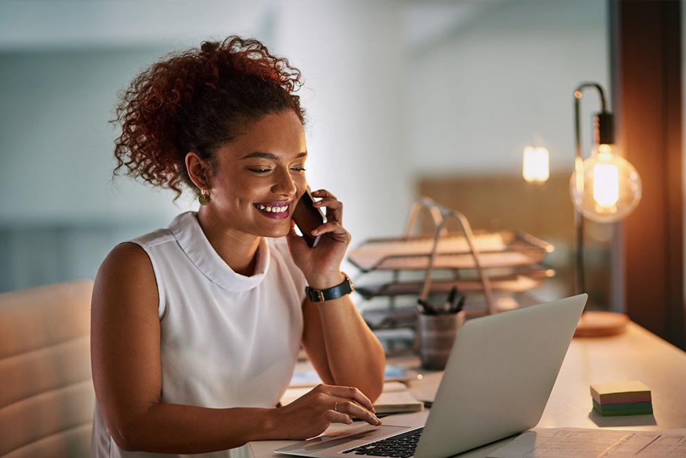 Jeune femme souriante au téléphone et au travail devant ordinateur