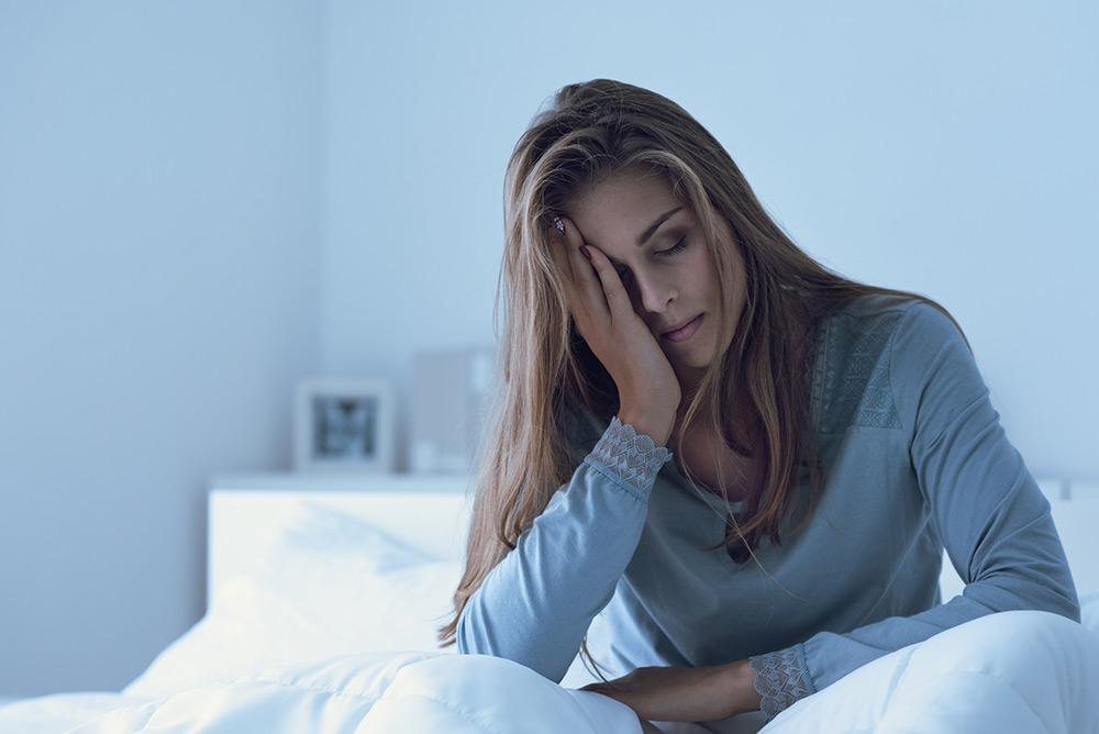 Jeune femme fatiguée qui se tient la tête au réveil dans son lit