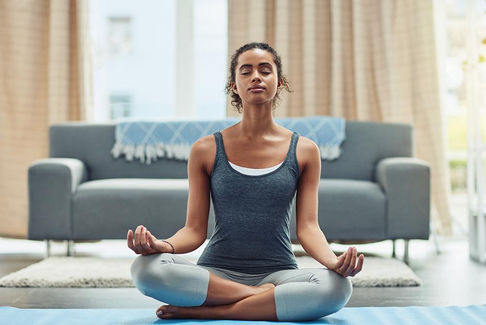 Jeune femme dans le salon pendant séance de yoga en position du lotus