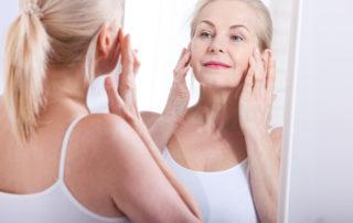 Femme observant sa peau dans un miroir