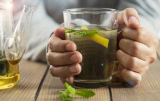 Plan rapproché sur verre de tisane avec des plantes et citron - phytothérapie