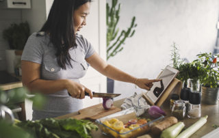 Jeune femme concoctant un plat à base de produits sains en suivant une recette en ligne sur tablette