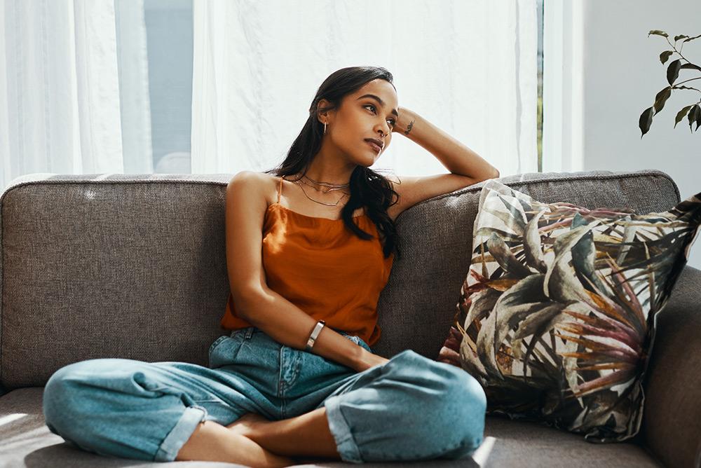 Jeune femme assise sur le canapé le regard fixé à l'horizon
