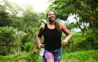 Jeune femme souriante lors de sa course à pied en forêt avec gourde à la main