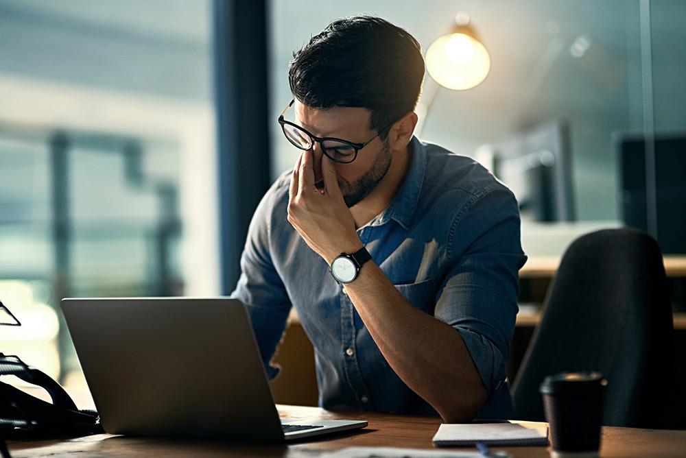 Jeune homme qui travaille devant son ordinateur fatigué et stressé