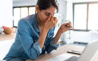 Jeune femme en télétravail devant l'ordinateur stressée et fatiguée