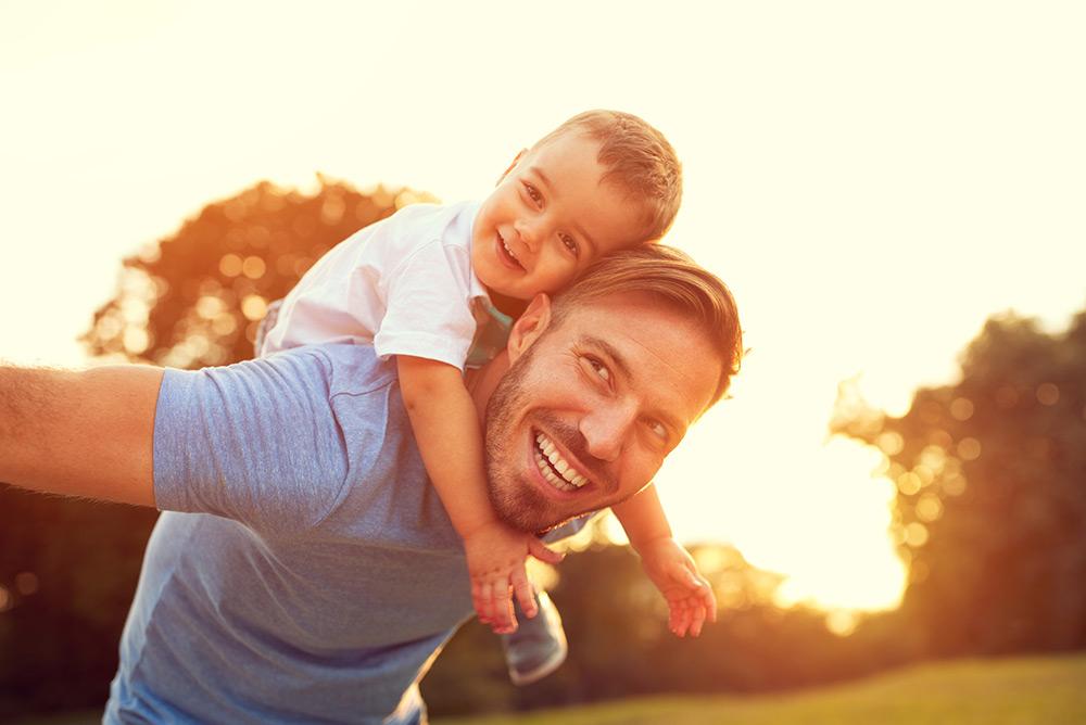 Jeune père avec son fils sur les épaules dans jardin profitant des rayons de soleil